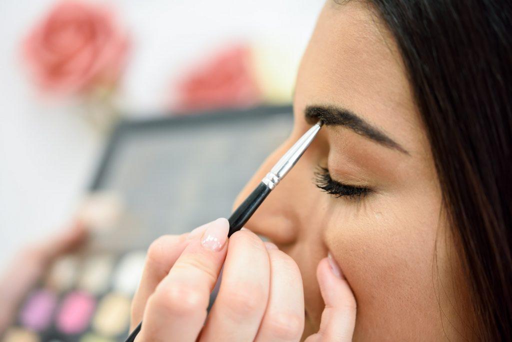 Makeup artist putting make-up on an woman's eyebrows
