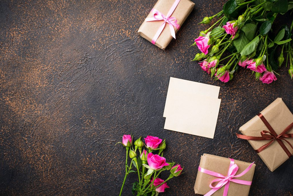 Pink roses, gift boxes and greeting card